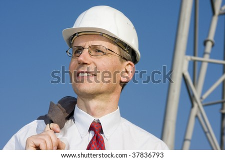 Smiling engineer with white hardhat on construction site - stock photo