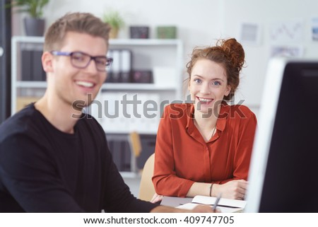 Smiling enthusiastic young businesswoman sitting at a desk working with a male colleague looking at the camera with a friendly smile - stock photo