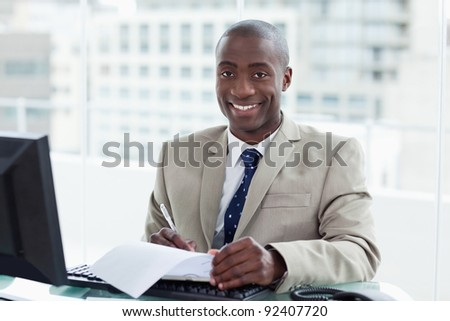 Smiling entrepreneur signing a document in his office - stock photo
