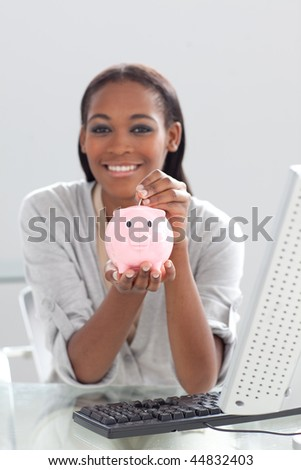 Smiling ethnic businesswoman saving money in a piggybank at her desk - stock photo