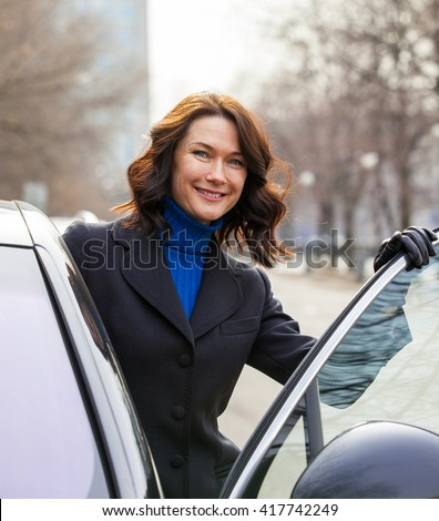 Smiling european middle-aged woman sits in the car - stock photo