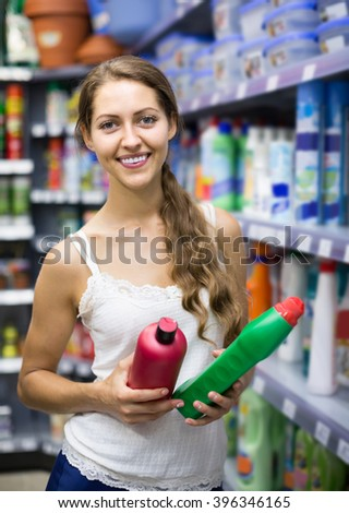 smiling european  people choose some detergents in the shop - stock photo