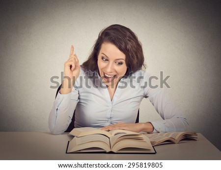 Smiling excited young woman reading a book has an idea pointing with finger up  - stock photo