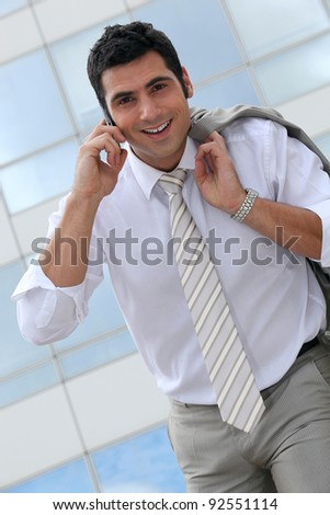 Smiling executive talking on a cellphone - stock photo