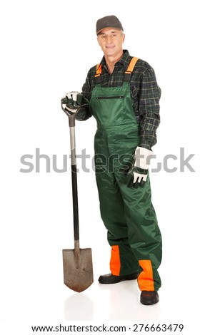 Smiling experienced gardener with a spade - stock photo