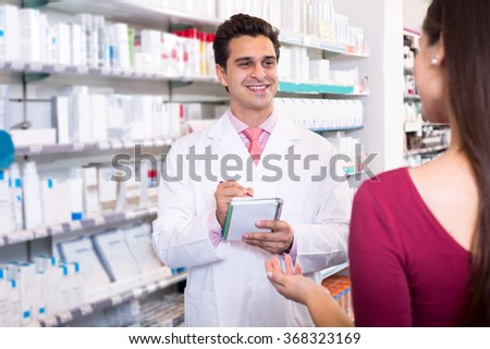 Smiling experienced pharmacist counseling female customer - stock photo