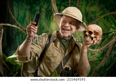 Smiling explorer taking a self portait with a skull in the jungle. - stock photo