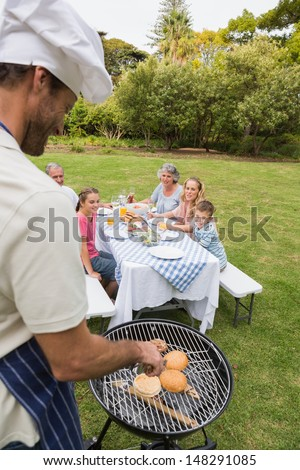 Smiling extended family having a barbecue being cooked by father in chefs hat outside in sunshine - stock photo