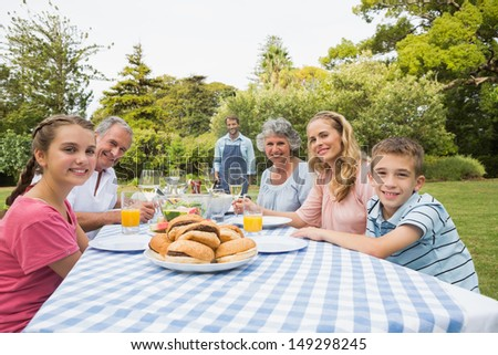 Smiling extended family waiting for barbecue being cooked by father smiling at camera - stock photo