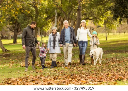 Smiling extended family walking together on an autumns day - stock photo