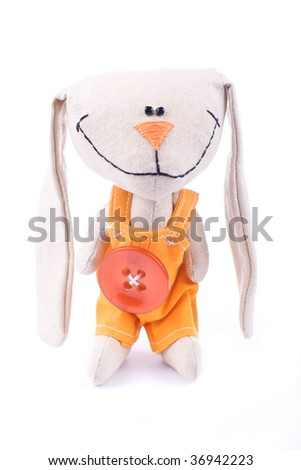 Smiling fabric hare toy in romper suit - stock photo
