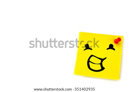 Smiling face against yellow pinned adhesive note