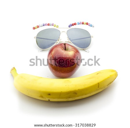 Smiling face formed by banana, sunglasses and an apple - stock photo