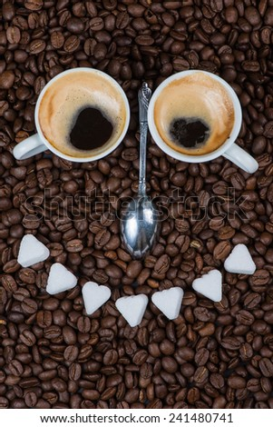 Smiling face made from cup of fresh coffee ,sugar and silver spoon - stock photo