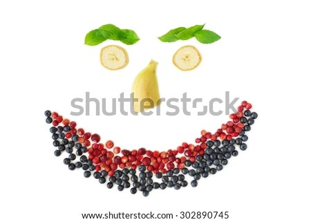 Smiling face made of fresh berries, banana and mint leaves, top view. Isolated - stock photo
