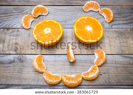 smiling face made with ripe citrus on an old wooden table - mandarins  - stock photo