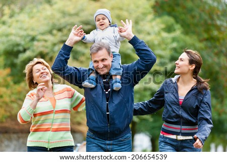Smiling family and grandparents in the countryside - stock photo