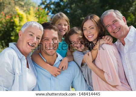 Smiling family and grandparents in the countryside embracing and smiling at camera - stock photo