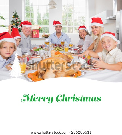 Smiling family around the dinner table at christmas against merry christmas - stock photo