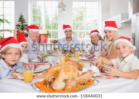 Smiling family around the dinner table at christmas wearing santa hats - stock photo