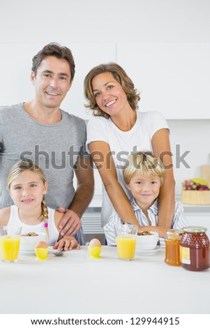 Smiling family at breakfast in the kitchen - stock photo