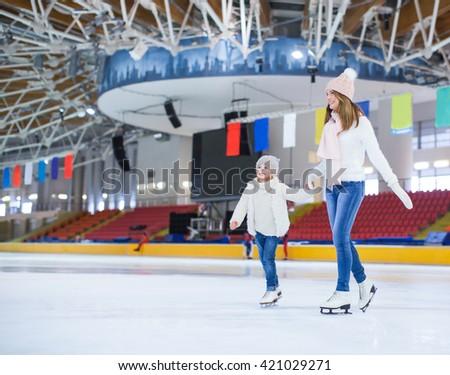 Smiling family at skating rink - stock photo