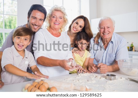 Smiling family baking together in the kitchen - stock photo