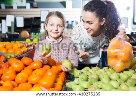 Smiling family customers buying ripe fruits in supermarket - stock photo