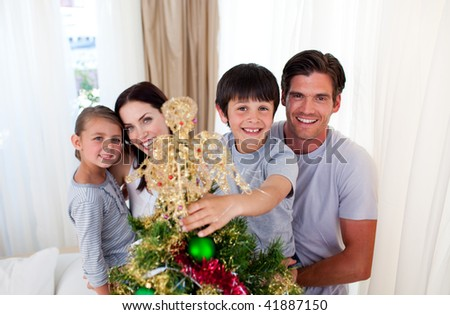 Smiling family decorating a Christmas tree in the living-room - stock photo