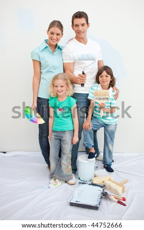 Smiling family decorating their house after move in