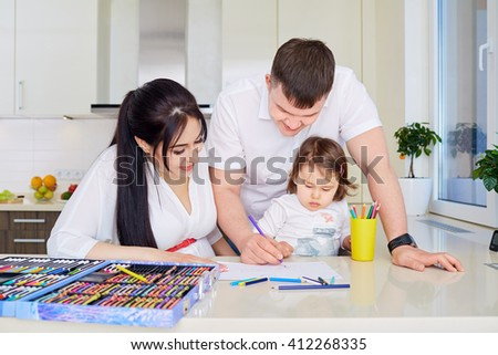 Smiling family drawing together in kitchen at home - stock photo