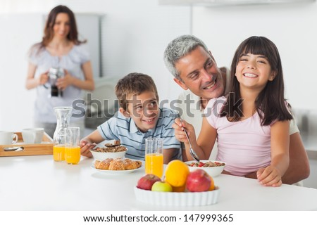 Smiling family eating breakfast in kitchen together at home - stock photo