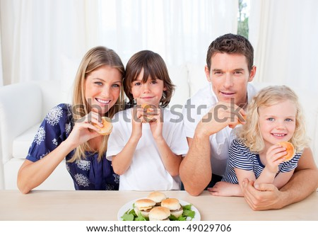 Smiling family eating burgers in the living room at home - stock photo