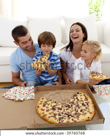 Smiling family eating pizza on sofa at home