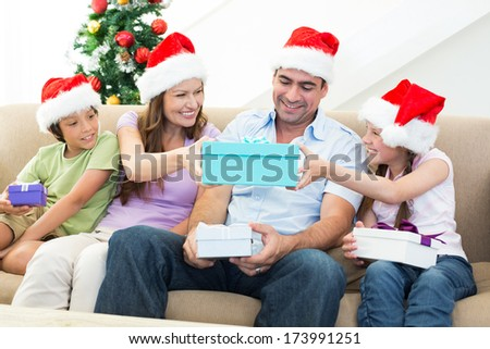 Smiling family exchanging Christmas gifts at home