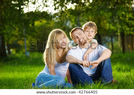 Smiling family has rest on a summer lawn - stock photo