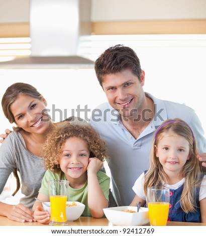 Smiling family having breakfast in their kitchen - stock photo