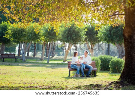 Smiling family in autumn park. Happy young parents with little kid sitting on the bench under the tree. - stock photo