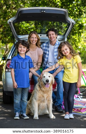 Smiling family in front of a car in the park - stock photo