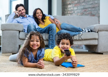 Smiling family in living room looking tv with children on the carpet - stock photo
