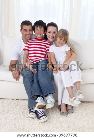 Smiling family in living-room sitting on sofa together - stock photo