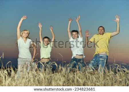 Smiling family jumping in field on sunset background