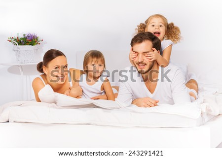 Smiling family laying on white bed in pajamas - stock photo