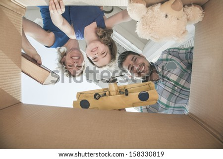 Smiling family looking into cardboard box - stock photo