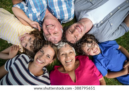 Smiling family lying in the grass in the garden - stock photo