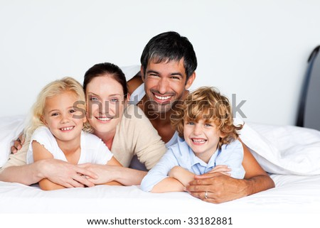 Smiling family lying together on bed - stock photo