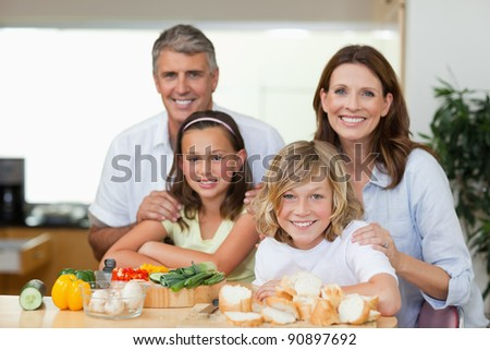 Smiling family making sandwiches together - stock photo