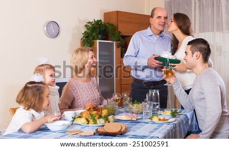 Smiling family member receiving present from relatives at table. Focus on mature woman - stock photo