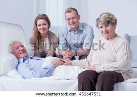 Smiling family members surrounding the bed of an old man in a very bright hospital room