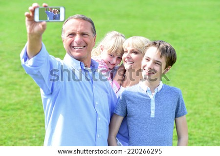 Smiling family of four taking selfie with smartphone - stock photo